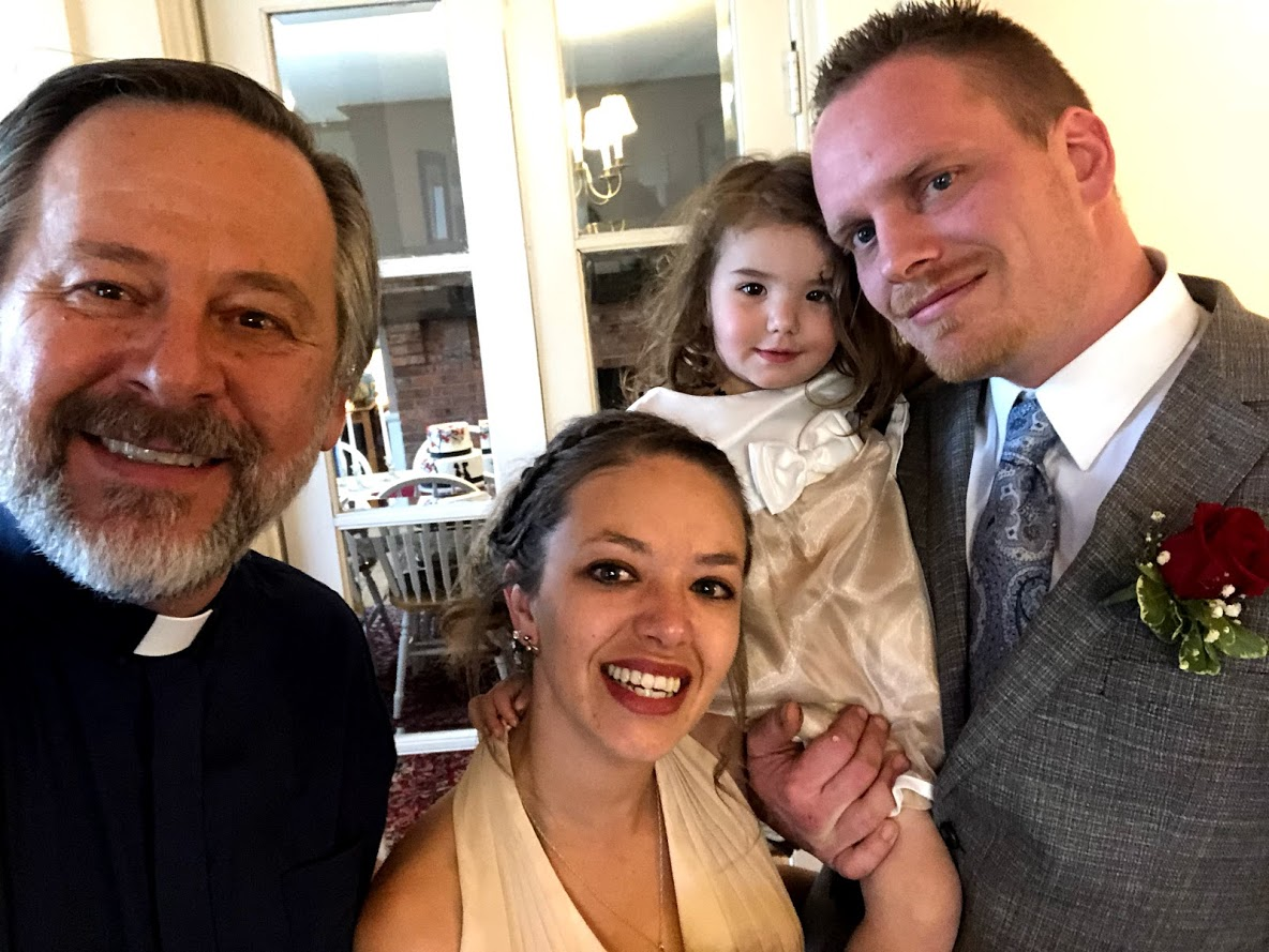selfie of wedding couple and child with minister