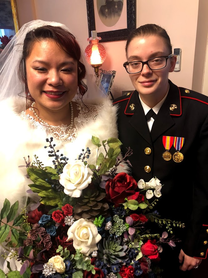 same sex wedding couple one in white lace dress holding bouquet of flowers, other in military dress uniform