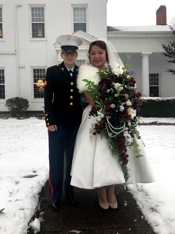 same sex wedding couple one in dress blues marine uniform, other in white dress with fur collar and large bouquet of flowers