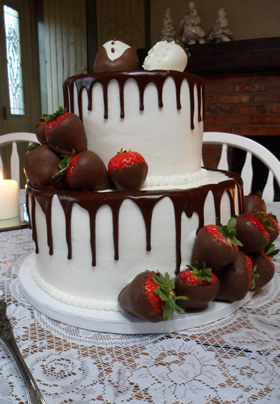 white wedding cake with dripping chocolate frosting and chocolate covered strawberries