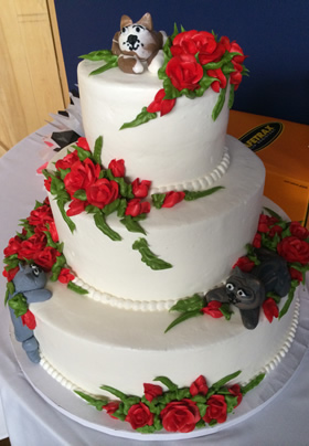 white wedding cake with red roses and greenery plus 3 cats