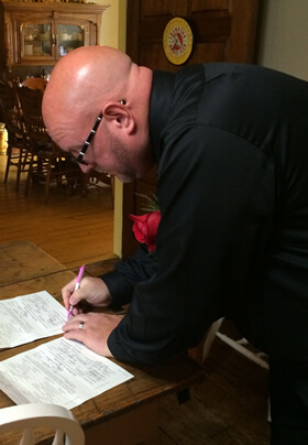 Bald groom with glasses and red boutonniere signing marriage papers