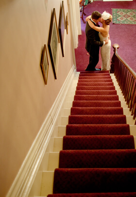 groom and bride kissing at the bottom of red carpet stairway