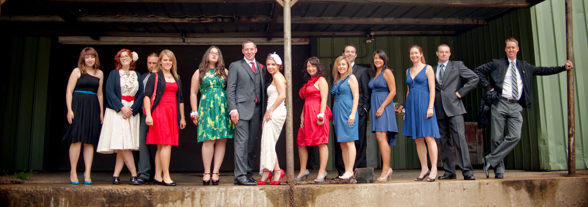 men and women in formal wear posing on an abandoned loading dock