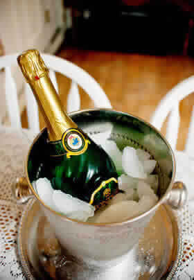 green bottle of champagne in a silver bucket with ice