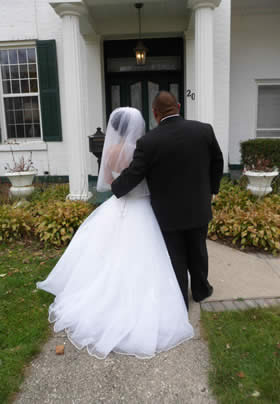 Back view of Bride in white with groom in black