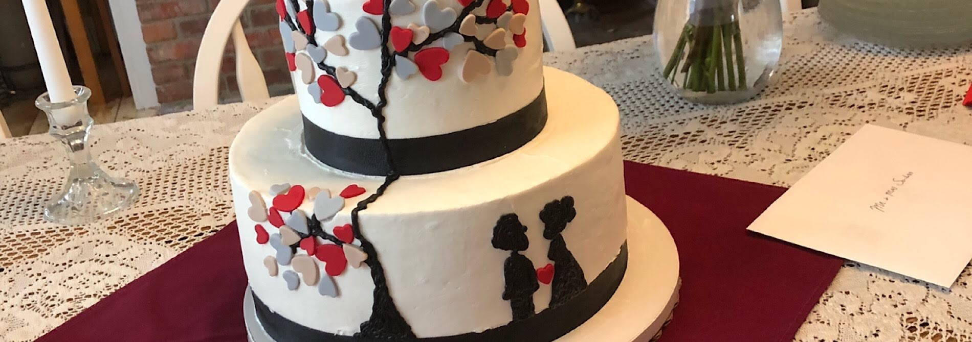 wedding cake with silhouette of boy and girl amidst multi-color heart shaped leaves