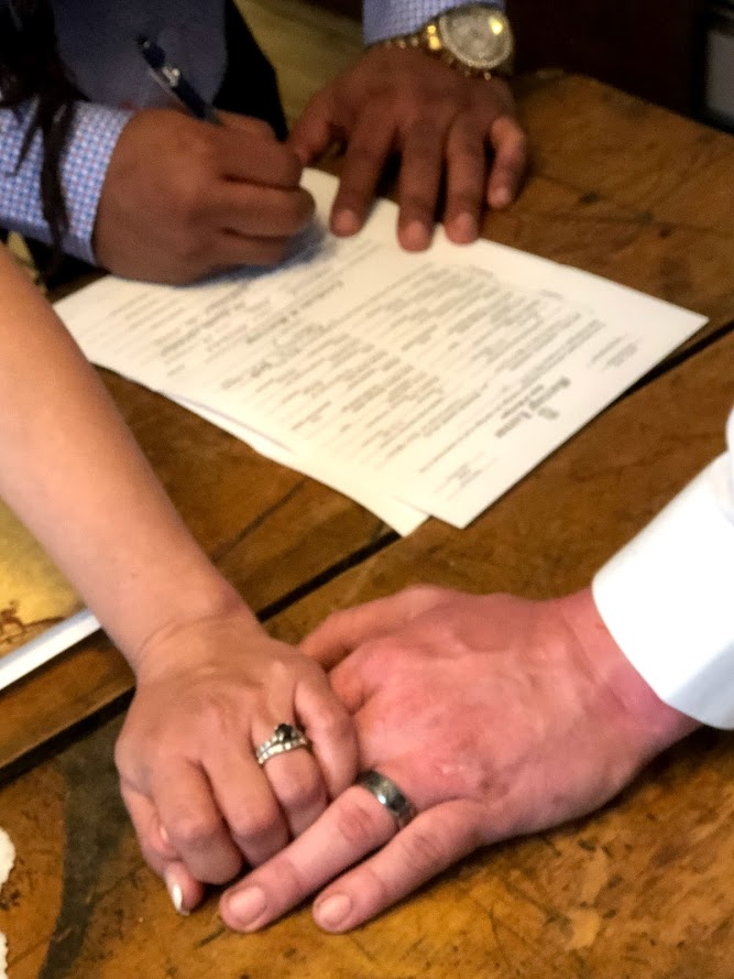 bride and groom holding hands with new wedding bands while witness signs documents in the background