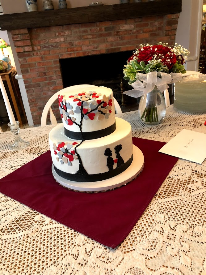 2 tier wedding cake with silhouette of bride and groom and multi-colored heart leaves on a tree