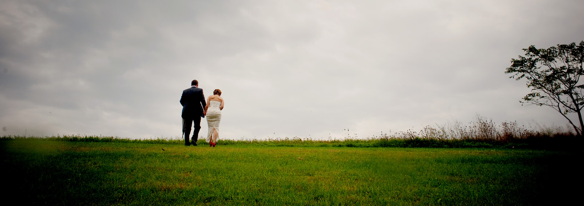 distant view of groom and bride walking away while holding hands at the top of an elevation of green grass against a gray sky